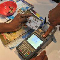 インドのハイデラバードで、生体認証によるIDシステム「アドハー」のカードを提示し、指紋をかざして預金を引き出す人(2017年1月18日撮影)。(c)AFP/Noah SEELAM