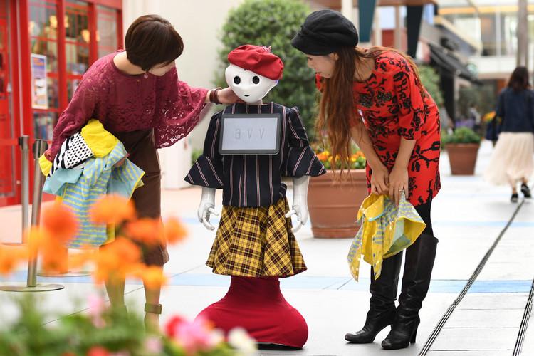 千葉県船橋市のショッピングモールで、秋らしい装いを披露するヒト型ロボット「ペッパー」。関係者がレインウエアを手に着替えの準備をする(2017年10月6日撮影)。(c)AFPBB News/Yoko Akiyo