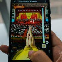 中国・上海で、習近平国家主席に拍手を送るオンラインゲームが表示されたスマートフォンの画面(2017年10月19日撮影)。(c)AFP/CHANDAN K