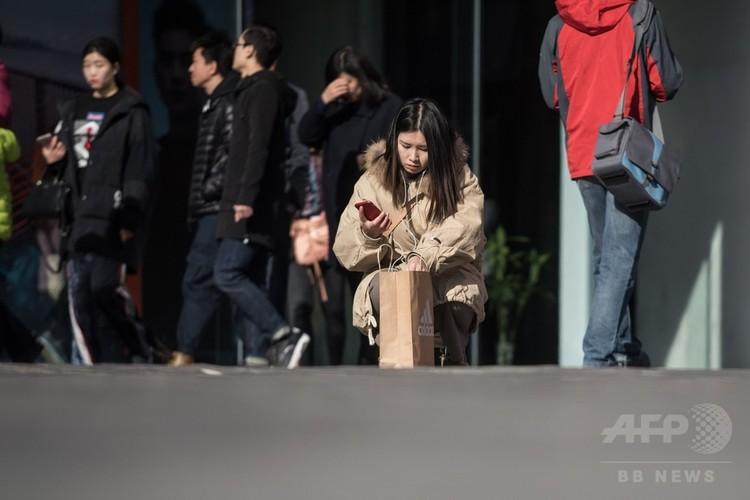中国北京でショッピングする人たち(2017年11月11日撮影)。(c)AFP/FRED DUFOUR