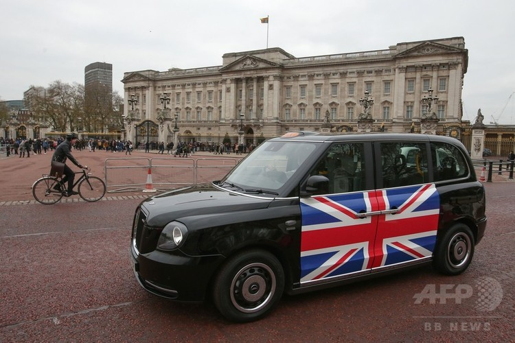 英ロンドンのバッキンガム宮殿近くを走行する新型電気タクシー「TX eCity」(2017年12月5日撮影)。(c)AFP/Daniel LEAL-OLIVAS