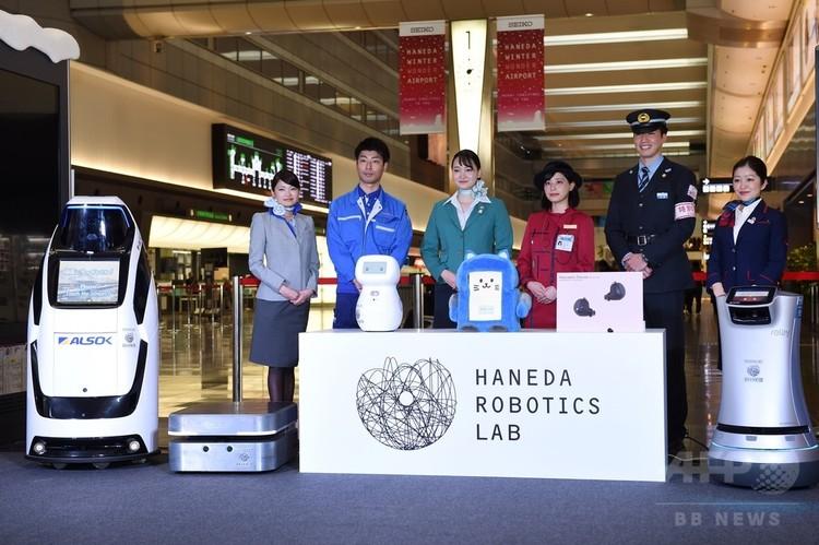 都内の羽田空港で行われた記者会見で、ロボットと一緒に写真撮影に臨む空港職員たち(2017年12月12日撮影)。(c)AFP/Kazuhiro NOGI