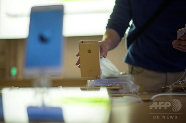 米アップルのiPhone6を手に取る男性(2014年9月14日撮影、資料写真)。(c)AFP PHOTO / Fred DUFOUR