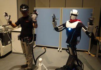 NTTdocomoの「5Gを使った遠隔ロボット操作」。人間の動きにロボットが同調し、ロボットの視覚や触覚の情報が人間に伝わる=2017年11月、日本科学未来館