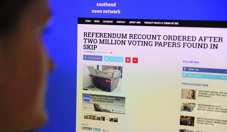 風刺目的の偽ニュースを読むジャーナリスト。英ロンドンで(2017年3月31日撮影、資料写真)。(c) AFP PHOTO / DANIEL SORABJI
