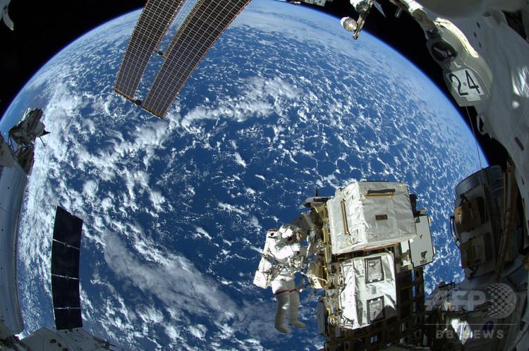 国際宇宙ステーション(ISS)で船外活動を行う米国のリード・ワイズマン飛行士(2014年10月8日撮影、資料写真)。(c)AFP PHOTO / NASA/ESA / ALEXANDER GERST