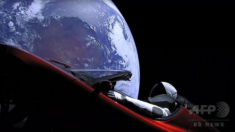 米宇宙開発企業スペースXが初めて打ち上げたファルコンヘビーロケットで地球周回軌道に入った、宇宙服を着たマネキン人形が乗った同社のイーロン・マスク最高経営責任者(CEO)が所有する赤いテスラ製オープンカー。スペースXが打ち上げ後に配信したライブストリーム動画から(2018年2月6日撮影)。(c)AFP PHOTO / SPACEX