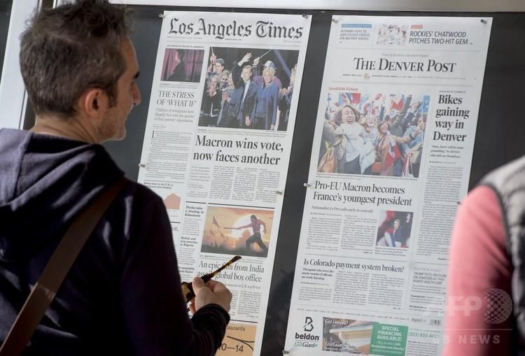 米首都ワシントンにある報道博物館「ニュージアム」の外に張られた新聞を見る人(2017年5月8日撮影、資料写真)。(c)AFP PHOTO / SAUL LOEB