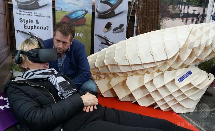 オランダのアムステルダムで開催された葬儀関連の見本市で、VR(仮想現実)ゴーグルを装着して自殺機器「サルコ」を体験する女性に機能を説明する、デザイナーのアレクサンダー・バニンク氏(2018年4月14日撮影)。(c)AFP/Jan HENNOP