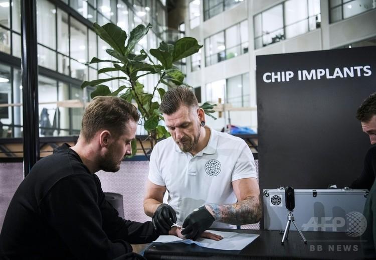 スウェーデンのストックホルムで、チップ移植を行うユアン・ウステルンド氏(右、2018年1月18日撮影)。(c)AFP PHOTO / Jonathan NACKSTRAND