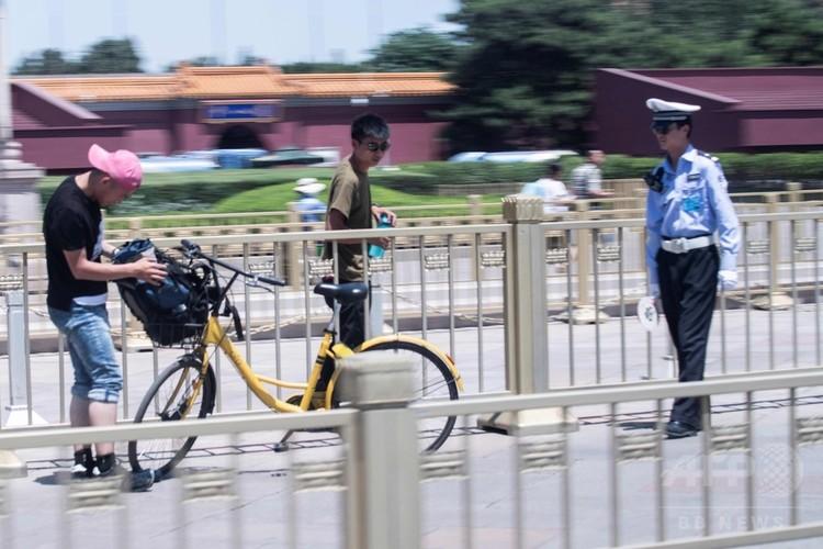 中国・北京の天安門広場で通行人の身元を確認する警官(2018年6月4日撮影)。(c) AFP PHOTO / FRED DUFOUR
