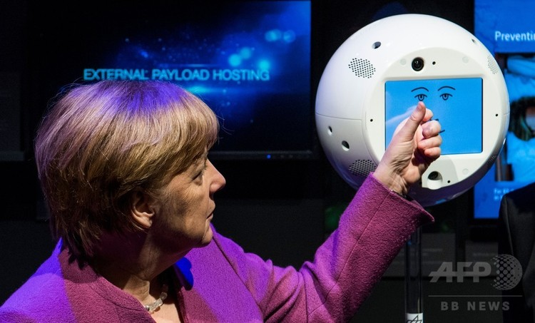 「CIMON」とやりとりするアンゲラ・メルケル独首相。ベルリン近郊のシューネフェルト空港で開催されたベルリン国際航空宇宙ショーで(2018年4月25日撮影)。(c)AFP/John MACDOUGALL