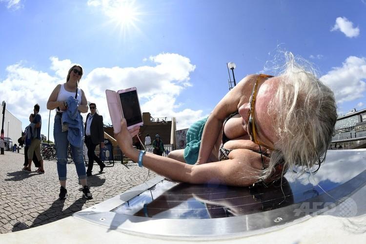 フィンランドの首都ヘルシンキで、太陽光パネルベンチの上で日光浴をしながら携帯電話を充電する女性(2018年7月9日撮影)。(c)AFP PHOTO / Lehtikuva / Martti Kainulainen