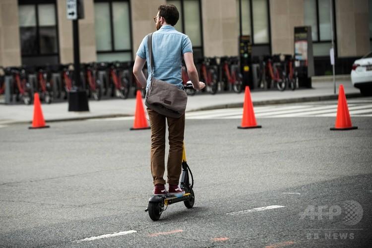 米ワシントンD.C.の通りで電動キックスケーターに乗る男性(2018年6月21日撮影)。(c)AFP PHOTO / Eric BARADAT