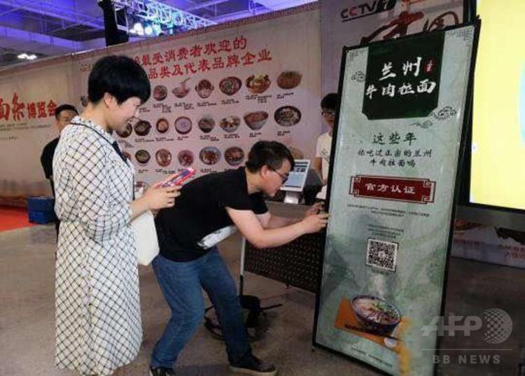 店舗のQRコードをスキャンすると、本場の蘭州牛肉ラーメンであるかどうかを調べられる(2018年6月23日撮影)。(c)CNS/魏建軍