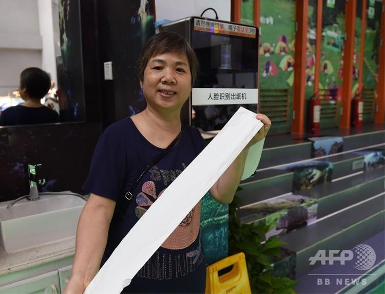顔識別によりトイレットペーパーを受け取った利用者(2018年8月23日撮影)。(c)CNS/周毅