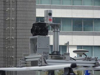 自動運転車両の天井部。左の黒いのが360度カメラ。円筒形の装置がレーザーセンサー、右の円盤状の装置がGPS