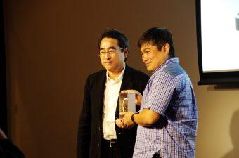 林郁・デジタルガレージ代表取締役から記念品の時計を受け取る