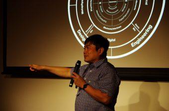 MITメディアラボで作成したサークル図の前で講演するJoi