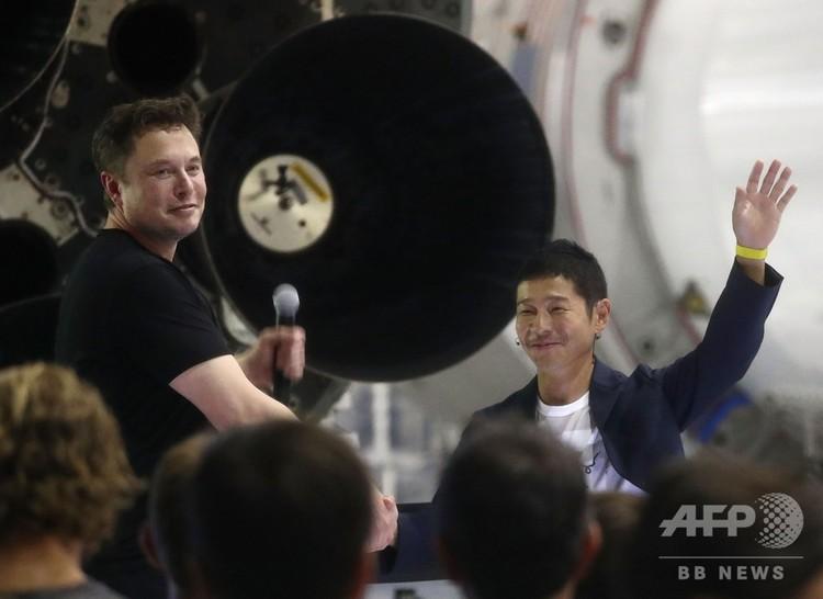 米カリフォルニア州ホーソーンで、米宇宙開発企業スペースXの最高経営責任者(CEO)イーロン・マスク氏(左)と握手する前澤友作氏(2018年9月17日撮影)。(c)Mario Tama/Getty Images/AFP