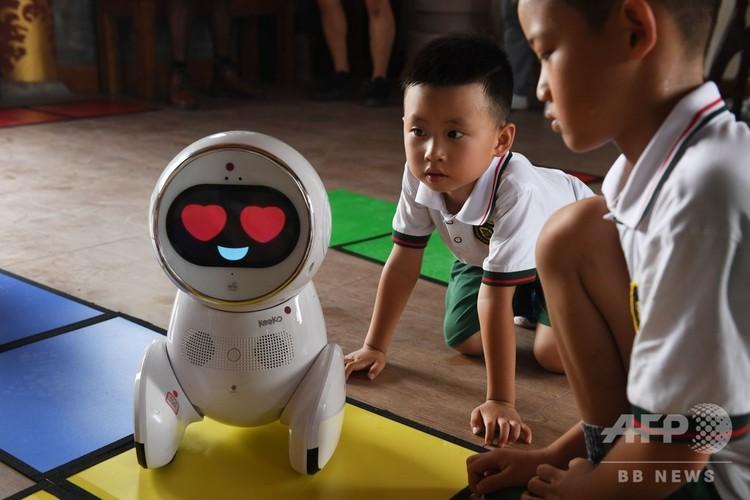 中国・北京の幼稚園で、ロボット先生「Keeko」を見る子どもたち(2018年7月30日撮影)。(c)GREG BAKER / AFP