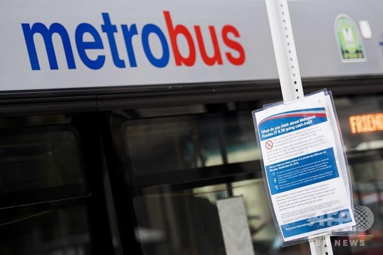 米首都ワシントンのバス停で、「バス料金のキャッシュレス化、あなたの意見は?」と書かれた張り紙(2018年10月24日撮影)。(c)Jim WATSON / AFP
