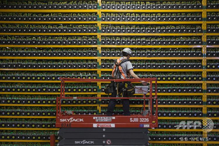 カナダ、ケベック州にある暗号通貨「マイニング(採掘)」企業で、暗号通貨獲得のための計算「マイニング」を行うコンピューター設備を見回る技術者(2018年3月19日撮影、資料写真)。(c)Lars Hagberg / AFP