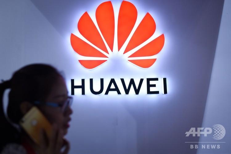 中国の通信機器大手、華為技術(ファーウェイ)のロゴの前を携帯電話で話しながら通り過ぎる女性。中国・北京にて(2018年7月8日撮影、資料写真)。(c)WANG ZHAO / AFP
