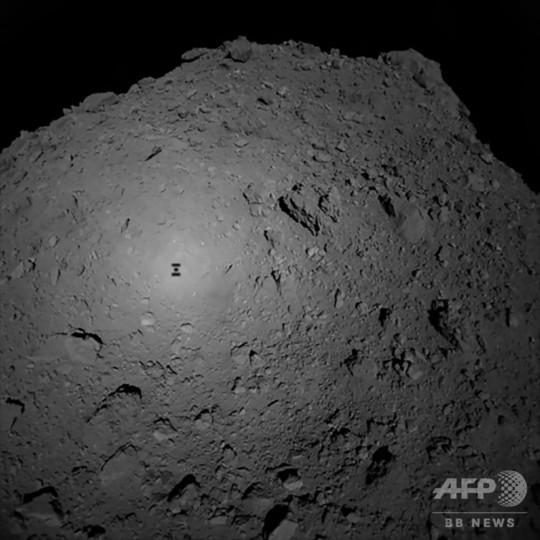 小惑星「リュウグウ」の表面に映った小惑星探査機「はやぶさ2」の影。はやぶさ2から撮影したもの(2018年10月3日撮影、同日提供、資料写真)。(c)AFP PHOTO / JAXA / FILES