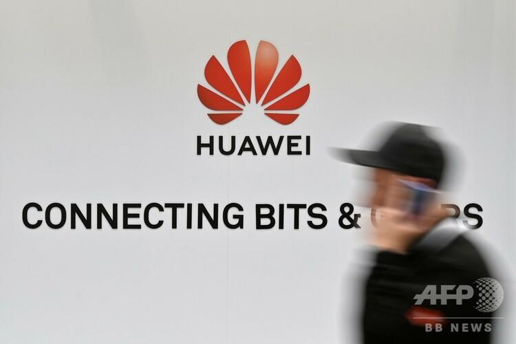 ドイツ・ハノーバーで開催されたテクノロジー系のイベントで、中国通信機器大手、華為技術(ファーウェイ)のロゴの前を通り過ぎる人(2019年4月1日撮影)。(c)JOHN MACDOUGALL / AFP