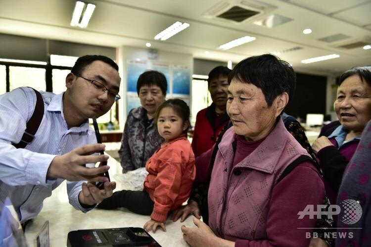 年金を受け取るための顔認証手続きを指導する社会保険担当の職員(2019年5月6日撮影)。(c)CNS/葛宜年
