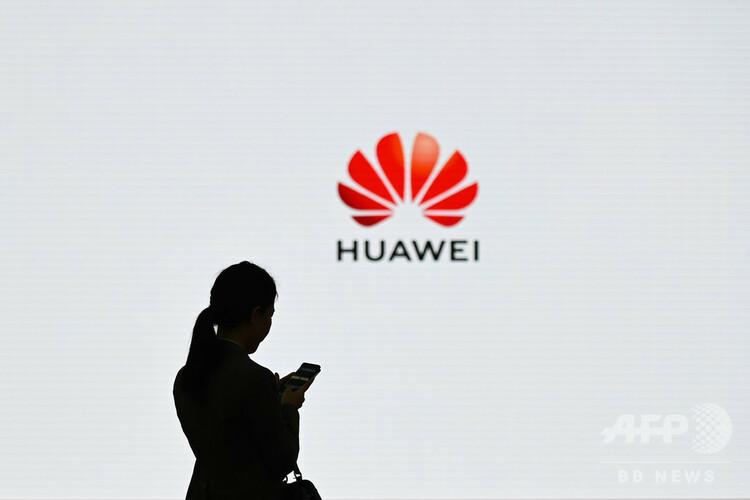 中国通信機器大手、華為技術(ファーウェイ)のロゴの前で携帯電話を操作する女性(2019年3月6日撮影)。(c)WANG ZHAO / AFP