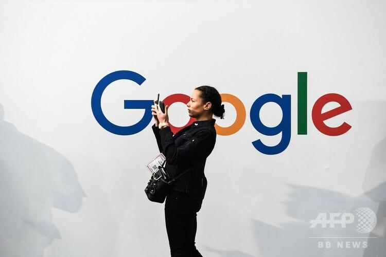 グーグルのロゴの前でスマートフォンで写真を撮る人(2019年5月16日撮影、資料写真)。(c)ALAIN JOCARD / AFP