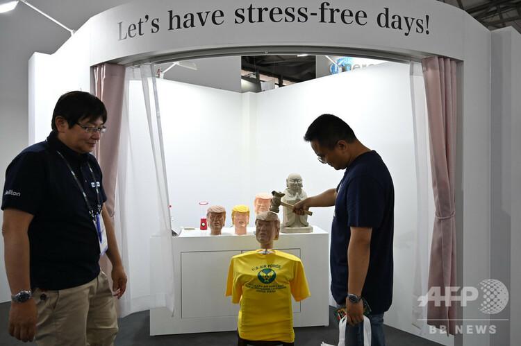 中国・上海で開催中の家電見本市「CESアジア」に日本のIT企業ソリトンシステムズが出展した「ストレス解消」ブースで、ドナルド・トランプ米大統領の頭部の模型をたたく男性(2019年6月11日撮影)。(c)HECTOR RETAMAL / AFP