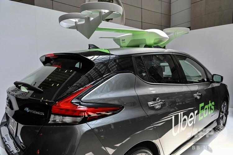 米ワシントンで開かれた開発者会議「ウーバー・エレベート・サミット」で披露された、食事配送サービス「ウーバーイーツ」用のドローンと配達車(2019年6月12日撮影)。(c)EVA HAMBACH / AFP