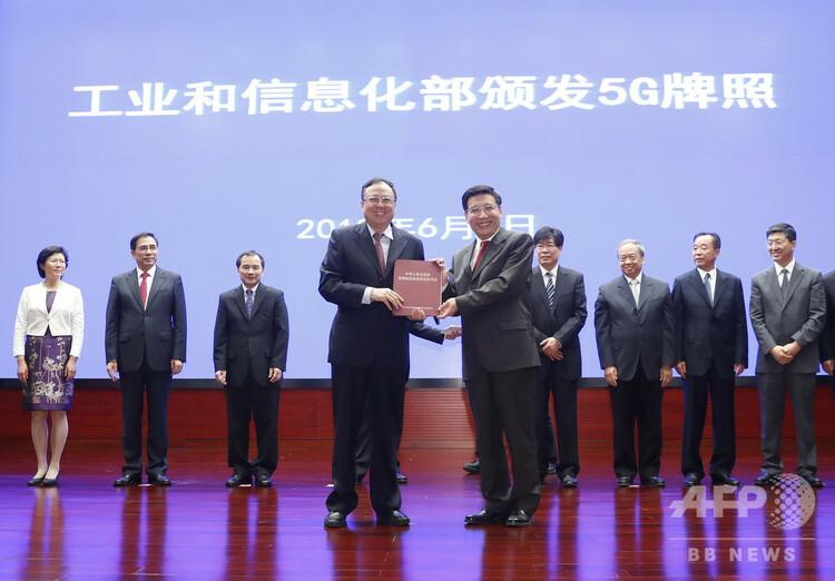 中国広電の趙景春董事長(中左)に5G許可証を交付する工業情報化部苗圩部長(右)(2019年6月6日撮影)。(c)CNS/杜洋