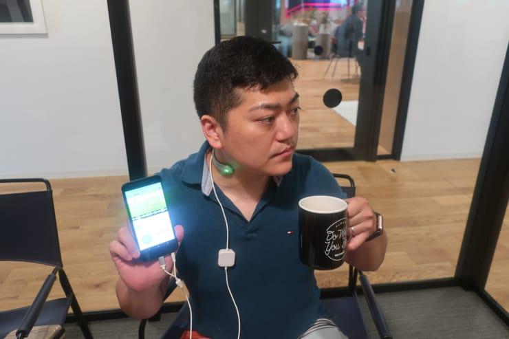 GOKURIを装着した状態でコーヒーを飲むと、嚥下を感知してセンサとアプリが緑色に発光する