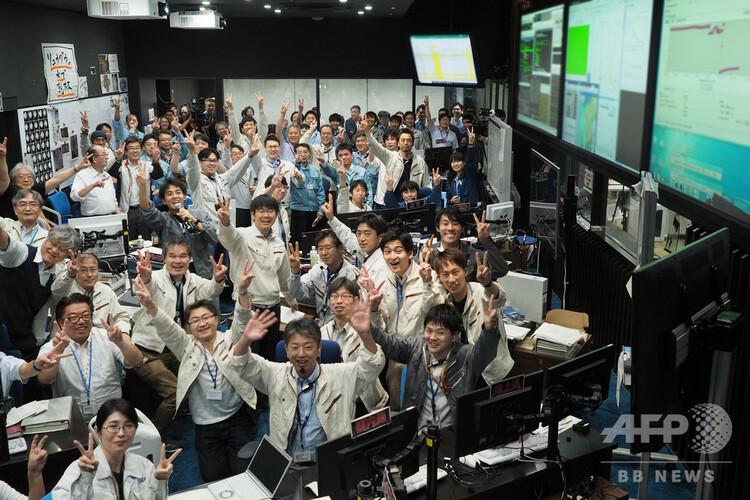 宇宙航空研究開発機構(JAXA)の宇宙科学研究所で、はやぶさ2の小惑星「リュウグウ」着陸成功を喜ぶ関係者ら(2019年7月11日撮影)。(c)Yutaka IIJIMA / ISAS-JAXA / AFP