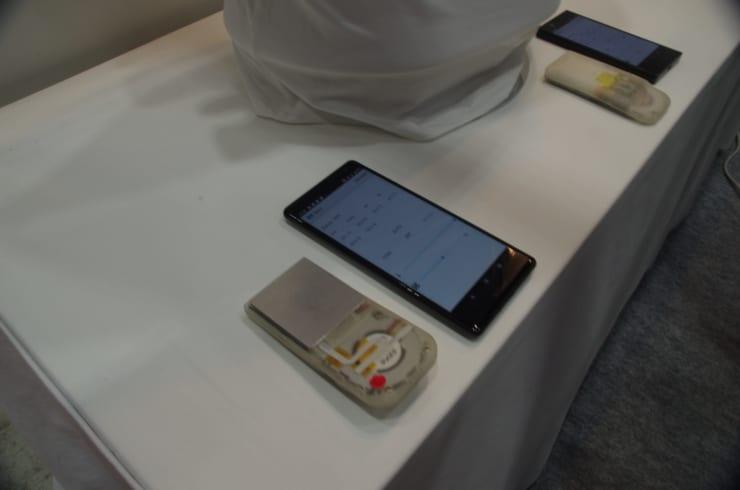 ペルチェ素子を利用した温冷装置とファンなどを組み込んだREON POCKET本体(展示用)と操作用スマホ