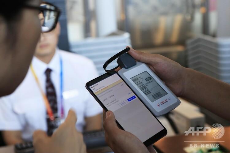 電源不要型電子手荷物タグの操作を説明する職員(2019年7月30日撮影)。(c)CNS/殷立勤