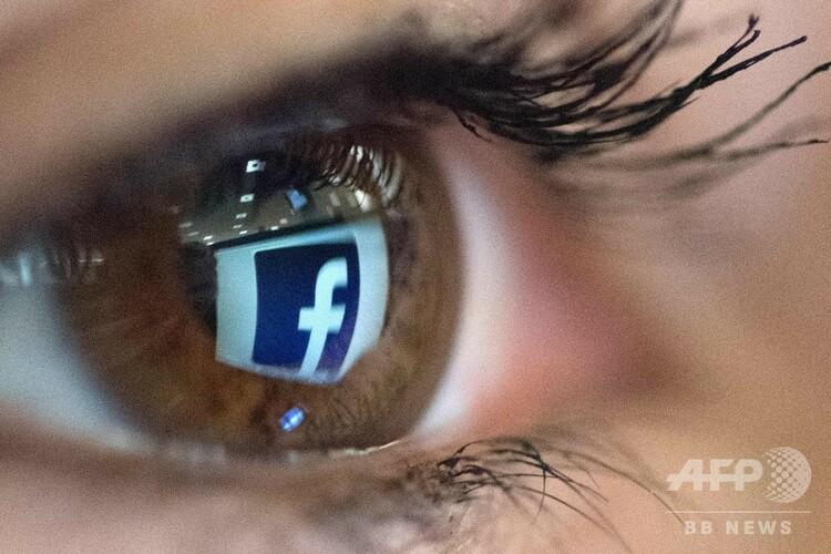 目の中に映し出された米フェイスブックのロゴ(2018年3月22日撮影、資料写真)。(c)Christophe SIMON / AFP