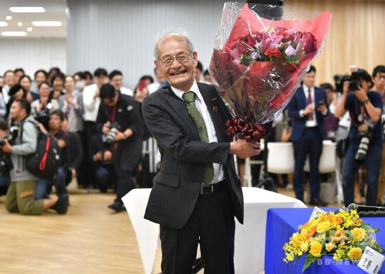 2019年ノーベル化学賞の受賞が決まり、記者会見の会場で花束を受け取った吉野彰氏(2019年10月9日撮影)。(c)Kazuhiro NOGI / AFP