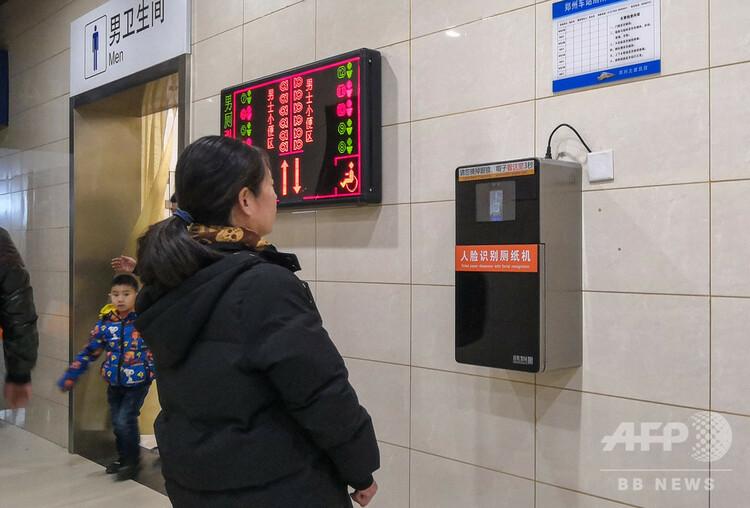 中国・河南省鄭州市の鄭州駅の公衆トイレの入り口に設置された顔認証技術が導入されたトイレットペーパーのディスペンサーを見つめる女性(2019年2月25日撮影、資料写真)。(c)STR / AFP