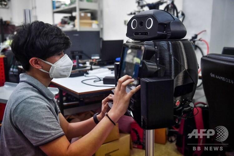 タイ首都バンコクのチュラロンコン大学で「忍者ロボット」のプログラム設定をする学生(2020年3月18日撮影)。(c)Lillian SUWANRUMPHA / AFP