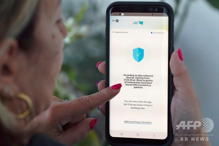 イスラエルの保健省がリリースしたスマートフォンアプリ「ハマゲン」を画面上で操作する女性(2020年3月29日撮影)。(c)JACK GUEZ / AFP