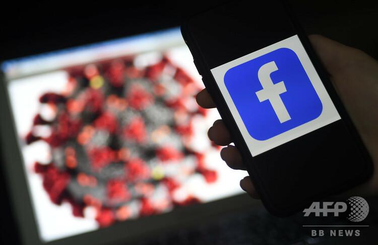 新型コロナウイルスのイラストを背後に、携帯電話の画面に表示されたフェイスブックのロゴ(2020年3月25日撮影)。(c)Olivier DOULIERY / AFP