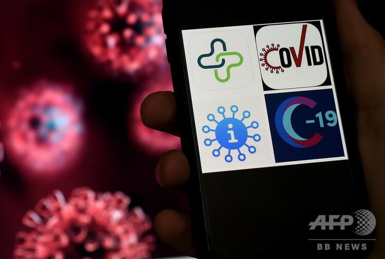スマートフォンの画面に表示された、新型コロナウイルス追跡アプリのロゴ(右、2020年4月10日撮影)。(c)Olivier DOULIERY / AFP