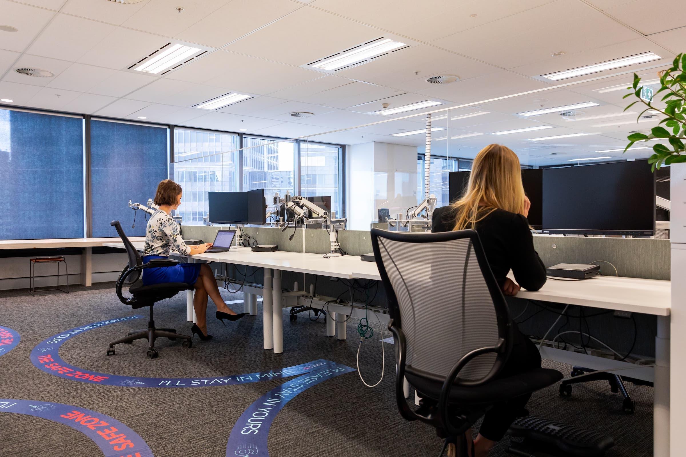 C&Wの提案する6フィートオフィス 床には距離を示す円形が、デスク前には飛沫防止のパネルが設置されている(シドニー/C&W提供)