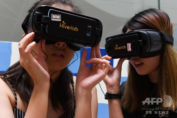 シンガポールで、バーチャルリアリティー(仮想現実、VR)のシミュレーションを体験する学生(2020年3月10日撮影)。(c)Catherine Lai / AFP