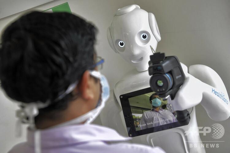 インド・ベンガルールの病院で、病院スタッフの体温を計測する熱探知カメラ搭載ロボット「ミトラ」(2020年5月2日撮影)。(c)Manjunath Kiran / AFP